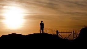 Homem que olha o por do sol Imagens de Stock