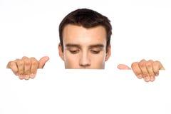 Homem que olha para baixo em uma placa branca foto de stock