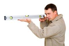 Homem que olha para nivelar a ferramenta fotografia de stock