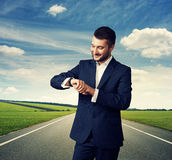 Homem que olha seu relógio sobre a estrada Fotografia de Stock Royalty Free