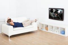 Homem que olha a tevê ao encontrar-se no sofá imagens de stock royalty free