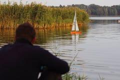 Homem que olha um barco rádio-controlado Fotografia de Stock Royalty Free