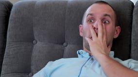 Homem que olha um filme de terror no sofá vídeos de arquivo