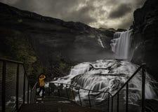 Homem que olha uma cachoeira fotografia de stock