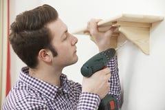 Homem que põe acima da prateleira de madeira em casa que usa Dril sem corda bonde Fotografia de Stock Royalty Free