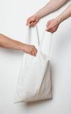Homem que põe algo no saco de matéria têxtil fotografia de stock royalty free
