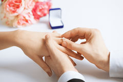 Homem que põe a aliança de casamento sobre a mão da mulher Imagem de Stock Royalty Free