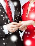 Homem que põe a aliança de casamento sobre a mão da mulher Fotografia de Stock