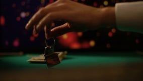 Homem que põe chaves da casa perto dos dólares sobre a tabela do pôquer, aposta arriscada do jogador tudo video estoque