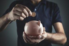 Homem que põe a moeda em um mealheiro Dinheiro da economia fotografia de stock royalty free
