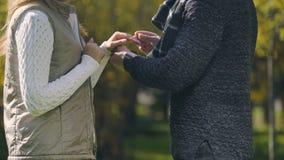 Homem que põe o anel de noivado sobre o dedo fêmea, acoplamento na proposta do parque do outono filme