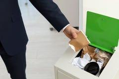 Homem que põe o copo de papel usado no escaninho de lixo, close up Reciclagem de resíduos foto de stock royalty free