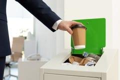 Homem que põe o copo de papel usado no escaninho de lixo, close up Reciclagem de resíduos fotografia de stock