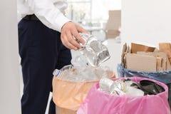 Homem que põe o recipiente usado da folha no escaninho de lixo no escritório Reciclagem de resíduos fotos de stock royalty free