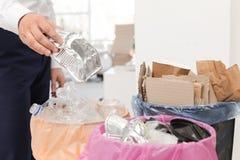 Homem que põe o recipiente usado da folha no escaninho de lixo no escritório Reciclagem de resíduos fotografia de stock royalty free