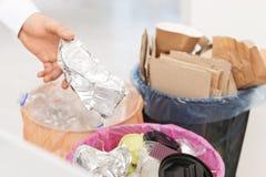 Homem que põe o recipiente usado da folha no escaninho de lixo Reciclagem de resíduos imagem de stock