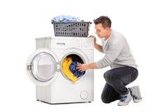 Homem que põe a roupa em uma máquina de lavar imagens de stock royalty free