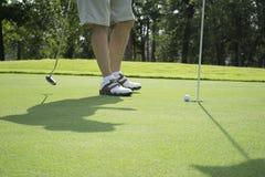 Homem que põe uma bola de golfe sobre o campo de golfe Imagens de Stock Royalty Free