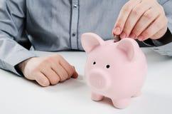 Homem que põr a moeda no banco piggy Fotografia de Stock
