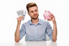Homem que põr o dinheiro no banco piggy imagens de stock royalty free