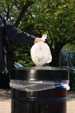 Homem que põr o lixo na lata de A Fotos de Stock Royalty Free