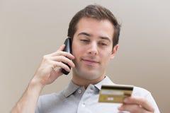Homem que paga com o cartão de crédito no telefone Fotografia de Stock
