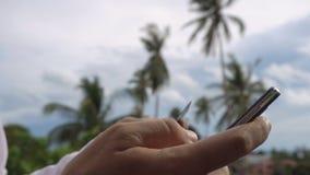 Homem que paga em linha com as palmeiras no backround Operação bancária do Internet video estoque