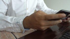 Homem que paga em linha a introdução do número de cartão de crédito no telefone celular Operação bancária do Internet vídeos de arquivo