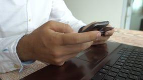 Homem que paga em linha a introdução do número de cartão de crédito no telefone celular Operação bancária do Internet video estoque