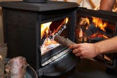Homem que põe o log no fogão ardente de madeira Fotografia de Stock Royalty Free