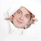 Homem que peeping através do furo no papel Fotografia de Stock Royalty Free
