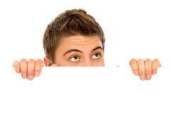 Homem que peeping sobre um quadro de avisos em branco Fotografia de Stock Royalty Free