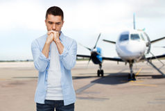 Homem que pensa sobre o avião no fundo da pista de decolagem Imagem de Stock Royalty Free