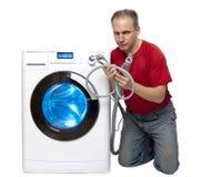 Homem que pensou do reparo ou da conexão da máquina de lavar perto da máquina de lavar nova imagem de stock