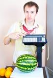 Homem que pesa a melancia no mercado Imagem de Stock Royalty Free
