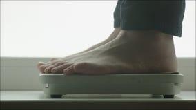 Homem que pesa-se com escalas de banheiro filme