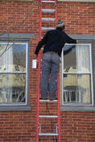 Homem que pinta Windows Foto de Stock