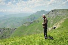 Homem que praying nas montanhas fotografia de stock