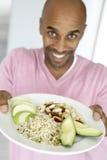 Homem que prende para fora uma placa com alimentos saudáveis Foto de Stock Royalty Free
