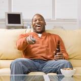 Homem que prende a televisão de observação de controle remoto Fotos de Stock Royalty Free