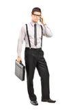 Homem que prende um breifcase e que fala em um móbil Imagens de Stock Royalty Free