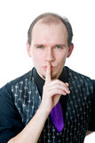 Homem que prende um dedo em seus bordos Imagens de Stock Royalty Free