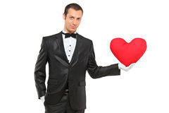 Homem que prende um descanso heart-shaped vermelho Foto de Stock