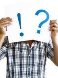 Homem que prende um ponto de interrogação e um ponto de exclamação Imagem de Stock Royalty Free