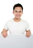 Homem que prende um quadro de avisos em branco. Imagem de Stock