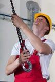 Homem que prepara o gancho do guindaste aos materiais de levantamento Fotos de Stock Royalty Free