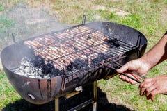 Homem que prepara reforços de carne de porco na grade Povos que fazem o assado e que têm o almoço na natureza no verão fotografia de stock