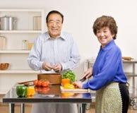 Homem que prepara a salada com a esposa na cozinha Imagens de Stock