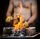 Homem que prepara um fogo para o assado Fotografia de Stock