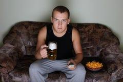Homem que presta atenção à tevê com cerveja Fotografia de Stock